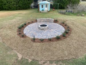 Circle paver firepit surrounded by pine straw and small green plants by DC Lawn & Landscape in Fairhope, AL