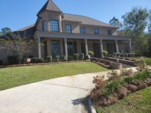 Front porch lined with bushes and straw by DC Lawn & Landscape in Fairhope, AL