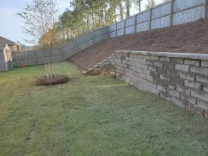 Landscape project that included sod, straw, trees and retaining wall by DC Lawn & Landscape in Fairhope, AL
