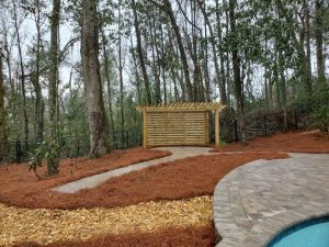 Front view of a pergola and rock path by DC Lawn & landscape in Fairhope, Alabama