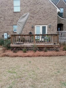 LD pine straw and plants decorating the side of a porch done by DC Lawn & Landscape in Fairhope, AL