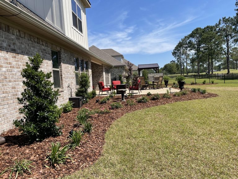 new bed with shrubs lining a patio done by DC lawn and landscape in Fairhope, Al